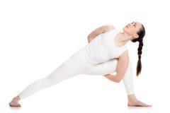 Utthita parsvakonasana. Sporty attractive young woman in white sportswear doing lunge exercise for spine, variation of utthita parshvakonasana with hands behind Stock Photos