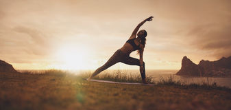Utthita Parsvakonasana yoga asana on the cliff at sunset. Horizontal shot of healthy female practicing Utthita Parsvakonasana yoga asana. Fitness woman Stock Images