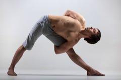 Utthita Trikonasana hard variation. Sporty young man working out, yoga, pilates, fitness training, doing Utthita Trikonasana, Extended Triangle pose with hands Stock Photo