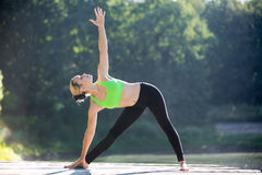 Utthita Trikonasana Pose. Beautiful sporty fit blond young woman in green sportswear working out outdoors on wooden deck, standing in Utthita Trikonasana Royalty Free Stock Photos