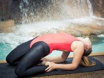 Utthita Ustrasana. Woman practicing yoga near waterfall. Extended Camel Pose. Utthita Ustrasana Stock Images