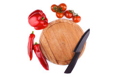 Сutting board with a knife, tomatoes and pepper around it. Сutting board with a knife, tomatoes and pepper around it on white background Stock Photos