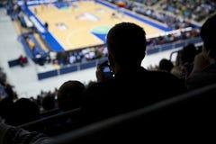 Uttråkad åskådare på en yrkesmässig basketmatch Arkivfoto