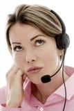 Uttråkad affärskvinna för attraktivt barn som använder en telefonhörlurar med mikrofon Royaltyfria Bilder