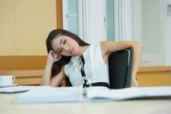 Uttråkad affärskvinna som ser mycket tråkig på hennes skrivbord Royaltyfri Foto