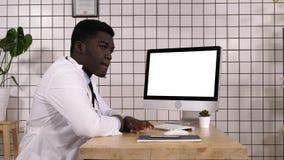Uttråkad afrikansk doktor som väntar på något vid datorskärmen Vit skärm arkivfoton