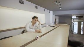 Uttråkad arbetare på arbetsplatsen lager videofilmer