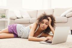 Uttråkad flicka för barn med den hemmastadda bärbara datorn arkivbild