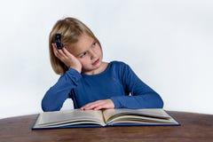 Uttråkad flicka med boken på vit bakgrund Royaltyfri Foto