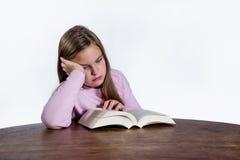 Uttråkad flicka med boken på vit bakgrund Royaltyfria Bilder