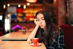 Uttråkad flicka som väntar på hennes datum i en coffee shop royaltyfri foto
