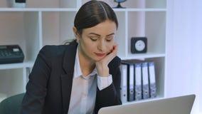 Uttråkad kontorsarbetare på skrivbordet som stirrar på datorskärmen med handen på hakan arkivfilmer