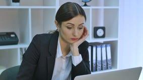 Uttråkad kontorsarbetare på skrivbordet som stirrar på datorskärmen med handen på hakan lager videofilmer