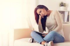 Uttråkad kvinna som använder ett bärbar datorsammanträde på en soffa royaltyfri fotografi