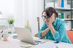 Uttråkad kvinna som arbetar med hennes bärbar dator Arkivbilder