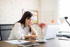 Uttråkad kvinna som i regeringsställning arbetar på bärbara datorn royaltyfria bilder
