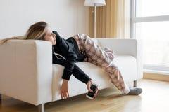 Uttråkad kvinna som ligger i soffa arkivbilder