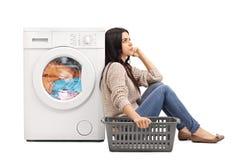 Uttråkad kvinna som väntar på tvätterit Arkivbild