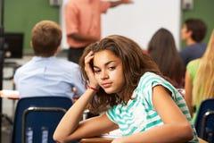 Uttråkad kvinnlig tonårs- elev i klassrum Arkivfoto
