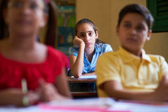 Uttråkad Latina Girl In för kvinnlig student grupp på skolan arkivfoto