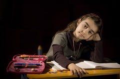 Uttråkad liten flicka som inte önskar att studera Arkivfoton