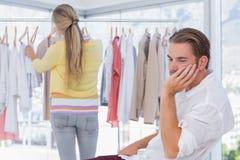 Uttråkad man, medan hans flickvän shoppar Royaltyfri Fotografi