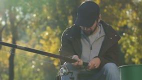 Uttråkad man som ta sig en tupplur under fiske, morgonaktivitet, fritids- meta arkivfilmer
