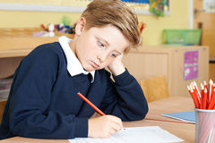 Uttråkad manlig grundskolaelev på skrivbordet royaltyfri fotografi