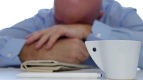 Uttråkad och trött man som sover med ett kaffe och en tidning på tabellen arkivfilmer