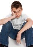 uttråkad pojke tröttad tryckt ned ensam sitting Arkivfoto