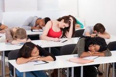 Uttråkad student med klasskompisar som sover på skrivbordet royaltyfria foton