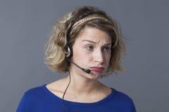 Uttråkad 20-talkvinna som bär en hörlurar med mikrofon för att svara påringningar Arkivfoto