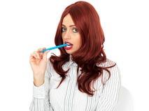 Uttråkad ung affärskvinna som tuggar på en penna Royaltyfria Bilder