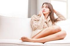 Uttråkad ung kvinna på hennes kopplade av soffa Royaltyfri Fotografi