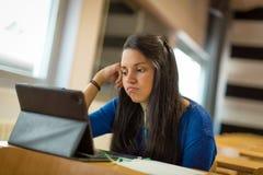 Uttråkad ung kvinnlig student på universitetklassrumet Henne ` s genom att använda minnestavlan och hörlurar för att ta anmärknin Arkivbild