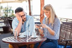 Uttråkad ung man som väntar på hans flickvän att stoppa använda telefonen royaltyfria bilder