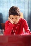 Uttråkad ung pojke som gör hans läxa Royaltyfri Bild