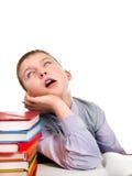 Uttråkad unge med böckerna royaltyfri bild