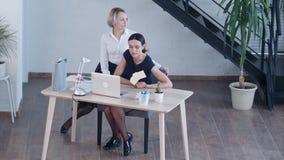 Uttråkade affärskvinnor som ser bort, medan sitta på stol lager videofilmer