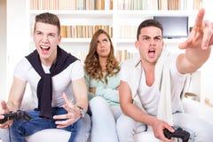 Uttråkade kvinnor mellan två tillfälliga passionerade män som spelar videospelet Royaltyfri Bild