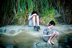 uttråkade pojkar vaggar den tonårs- sanden Arkivbild