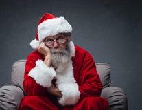 Uttråkade Santa Claus på fåtöljen Arkivbild