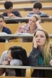 Uttråkade studenter som sitter i en hörsal Arkivbild