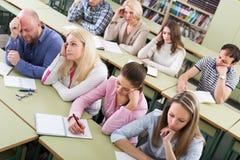 Uttråkade studenter som sitter på kursen royaltyfri bild