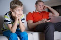 Uttråkat barn med hans fadersammanträde och hållande ögonen på tv Arkivbild
