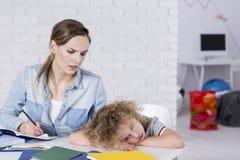Uttråkat barn på skrivbordet Royaltyfria Bilder