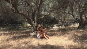 Uttråkat barn som spelar i den Olive Orchard Meditative Kid Little flickan som kopplar av vid trädet royaltyfria bilder