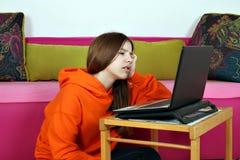 Uttråkat hållande ögonen på massmediainnehåll för tonårs- flicka på bärbara datorn royaltyfria foton
