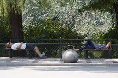 Uttröttade besökare som sover på offentliga stolar Royaltyfri Bild