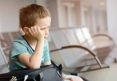 Uttråkad barnpojke som väntar på flygplatsen Fotografering för Bildbyråer
